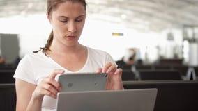Trabalho da mulher no portátil na sala de espera do aeroporto Mulher de negócios ocasional no smartphone do uso da viagem de negó filme