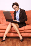 Trabalho de assento da mulher no computador superior de regaço Foto de Stock