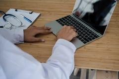 Trabalho de assento do doutor novo com o portátil na mesa fotos de stock