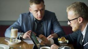 Trabalho de dois homens de negócios na altura da sobremesa no café filme
