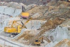 Trabalho de máquinas escavadoras pesadas da mineração na pedreira gredosa Fotos de Stock
