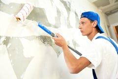 Trabalho de renovação do pintor em casa com prima foto de stock