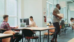 Trabalho de terminação do homem negro no espaço coworking Laptop de fechamento do homem sério filme