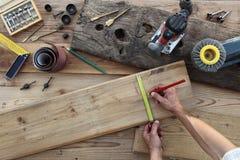 Trabalho do carpinteiro das mãos a madeira, medindo com medidor da fita e pena imagens de stock