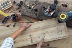 Trabalho do carpinteiro das mãos a madeira, placas de madeira rústicas velhas da liga fotos de stock