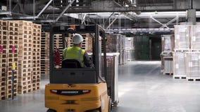 Trabalho do elevador da forquilha no armazém grande grampo Trabalhador do warehouseman com empilhadeira Cremalheira do armazém da video estoque