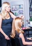 Trabalho do estilista no cabelo feliz da mulher no salão de beleza fotos de stock royalty free