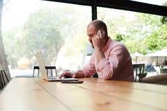Trabalho do estudante masculino no touchpad do computador ao falar no telefone esperto Fotos de Stock