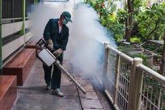 Trabalho do homem que enevoa-se para eliminar o mosquito para impedir o vírus espalhado da febre e do zika de dengue Fotografia de Stock Royalty Free