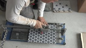 Trabalho do homem do trabalhador da construção com a telha de assoalho que corta o equipamento vídeos de arquivo