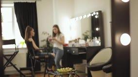 Trabalho do maquilhador com modelo no estúdio da beleza A forma faz para o modelo elegante do ruivo vídeos de arquivo