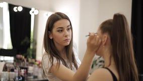 Trabalho do maquilhador em seu estúdio da beleza A mulher que aplica-se pelo profissional compõe o mestre Bonito compõe o artista video estoque