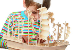 Trabalho do menino com zelo na casca do barco artificial Imagens de Stock Royalty Free