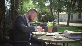 Trabalho do revestimento do homem de negócios durante o almoço outdoor tiro do steadicam filme