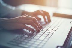 Trabalho em casa com a mulher do portátil que escreve um blogue Mãos fêmeas no teclado Fotografia de Stock Royalty Free