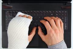 Trabalho em um caderno com ferimento de mão Imagem de Stock Royalty Free