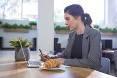 Trabalho executivo fêmea na mesa ao comer o café da manhã Fotografia de Stock