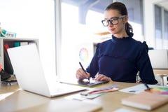 Trabalho executivo fêmea sobre o portátil e a tabuleta gráfica em sua mesa Imagens de Stock