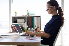 Trabalho executivo fêmea sobre o portátil e a tabuleta gráfica em sua mesa Imagem de Stock