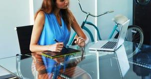 Trabalho executivo fêmea sobre o portátil e a tabuleta gráfica na mesa 4k filme