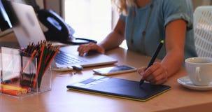 Trabalho executivo fêmea sobre a tabuleta gráfica em sua mesa 4k vídeos de arquivo
