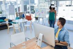 Trabalho executivo masculino no computador quando executivo fêmea que usa auriculares da realidade virtual fotografia de stock royalty free