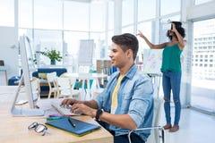 Trabalho executivo masculino no computador quando executivo fêmea que usa auriculares da realidade virtual foto de stock royalty free