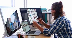 Trabalho executivo masculino sobre o portátil e a tabuleta gráfica em sua mesa 4k video estoque
