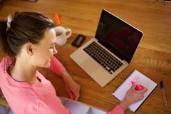 Trabalho fêmea novo em sua mesa Fotografia de Stock