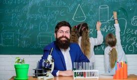 Trabalho farpado do professor do homem com microscópio e tubos de ensaio na sala de aula da biologia Explicando a biologia às cri foto de stock royalty free