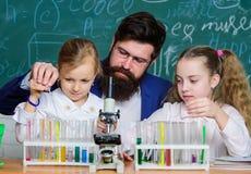 Trabalho farpado do professor do homem com microsc?pio e tubos de ensaio na sala de aula da biologia Como interessar crian?as est fotos de stock royalty free
