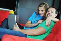 Trabalho feliz dos pares no portátil em casa Fotografia de Stock Royalty Free