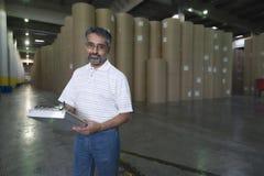 Trabalho masculino contra Rolls enorme do papel na fábrica Fotos de Stock