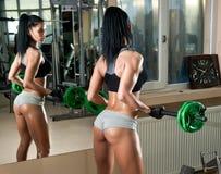 Trabalho moreno lindo em seus músculos em um gym, reflexão de espelho Mulher da aptidão que faz o exercício Menina desportiva que Fotografia de Stock
