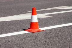 Trabalho na estrada Cone da construção Trafique o cone, com as listras brancas e alaranjadas no asfalto Sinais da rua e de tráfeg foto de stock royalty free