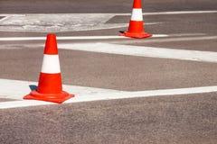 Trabalho na estrada Cones da construção Trafique o cone, com as listras brancas e alaranjadas no asfalto Sinais da rua e de tráfe foto de stock
