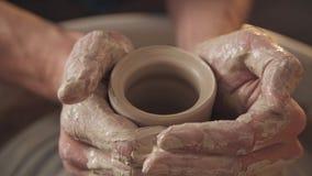 Trabalho na oficina da cerâmica: os mercadorias da argila no ` s do oleiro rodam Foto de Stock