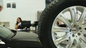 Trabalho na sala de exposições O gerente de vendas no negócio trabalha em uma mesa No primeiro plano do carro e da roda, filme