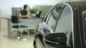 Trabalho na sala de exposições O gerente de vendas no negócio trabalha em uma mesa No primeiro plano do carro, o gerente da image filme