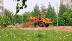 Trabalho no canteiro de obras A escavadora ajunta a cubeta na terra vídeos de arquivo