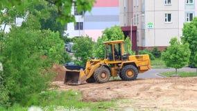 Trabalho no canteiro de obras A escavadora ajunta a cubeta na terra filme