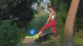Trabalho no corpo, mulher atrativa saudável que executa esticando o exercício durante esportes treinando na natureza na ponte de  video estoque