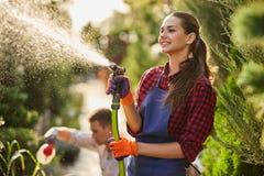 Trabalho no jardim O jardineiro de sorriso da menina pulveriza a água e um indivíduo pulveriza o adubo em plantas no berçário bon fotografia de stock
