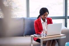 Trabalho ocupado da mulher de negócios africana em seu caderno na sala de estar do negócio Foto de Stock Royalty Free