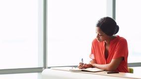 Trabalho ocupado do escritor africano fêmea quando assentado ao lado de uma janela imagens de stock