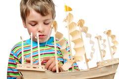 Trabalho pequeno do menino com zelo no navio artificial Fotos de Stock Royalty Free