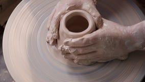 Trabalho profissional do mestre do oleiro usando a roda de gerencio para formar o barro da argila no processo real da faculdade c video estoque