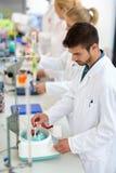 Trabalho químico dos técnicos com os tubos de ensaio no laboratório Imagem de Stock