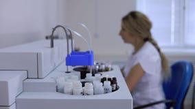 Trabalho remoto do assistente de laboratório no computador que controla o analisador químico filme
