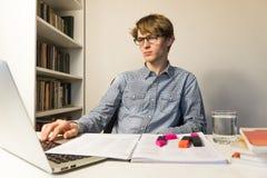 Trabalhos da pessoa masculina com livros e portátil na atribuição ou no projeto home fotografia de stock